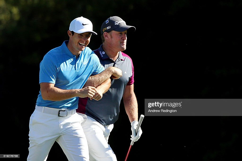 Rory McIlroy of Northern Ireland and Jamie Donaldson of Wales lock arms during a practice round prior to the start of the 2016 Masters Tournament at...