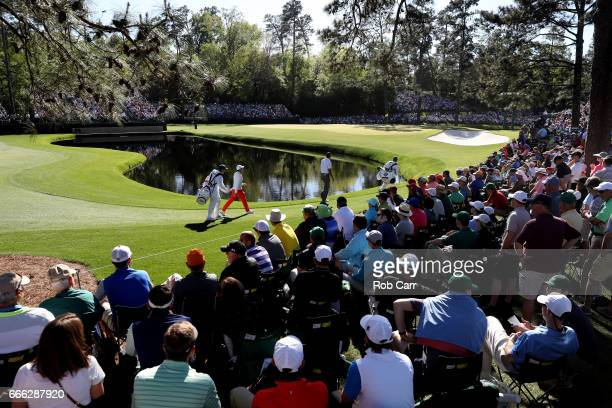 Rory McIlroy of Northern Ireland and Matt Kuchar of the United States walk to the 15th green during the third round of the 2017 Masters Tournament at...