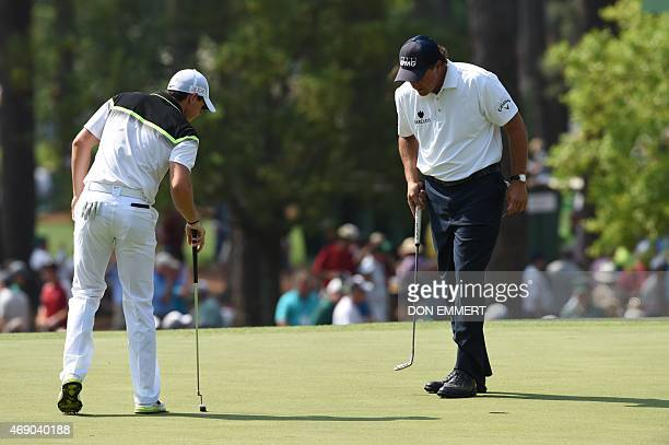 Rory McIlroy of Northern Ireland and Phil Mickelson of the US look at the green on the 3rd hole during Round 1 of the 79th Masters Golf Tournament at...