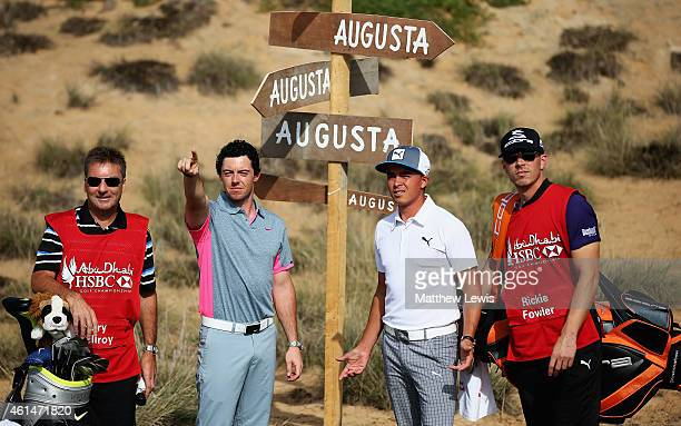 Rory McIlroy of Northern Ireland and Rickie Fowler of the USA take some advice from caddies JP Fitzgerald and Joe Skovron during a photocall prior to...