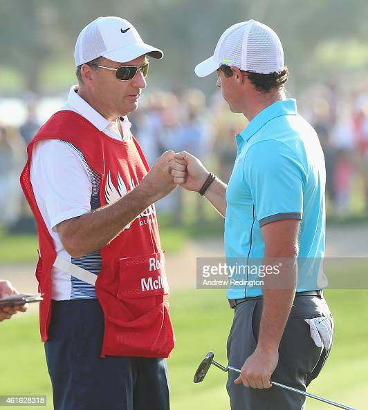 Rory McIlroy of Northern Ireland bumps knuckles with his caddie JP Fitzgerald after his birdie on the 18th hole during the second round of the Abu...