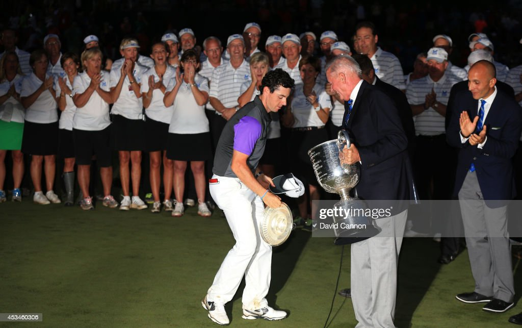 Rory McIlroy of Northern Ireland catches the lid of the Wanamaker trophy as PGA of America President Ted Bishop looks on after his onestroke victory...