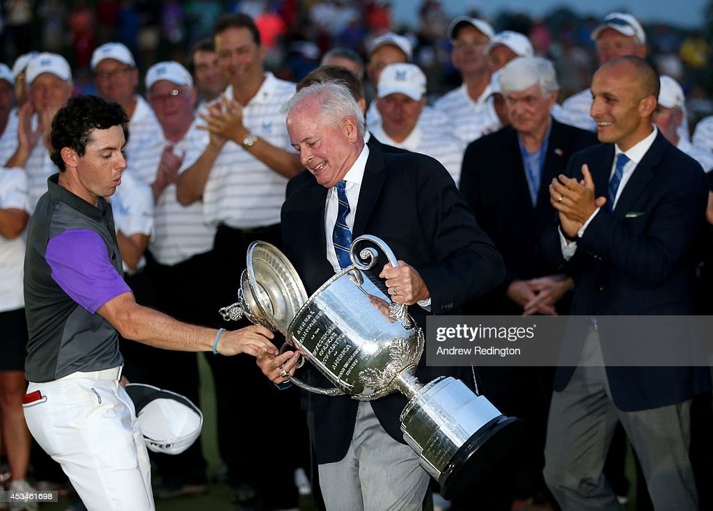Rory McIlroy of Northern Ireland catches the lid of the Wanamaker trophy as PGA of America President Ted Bishop holds the trophy after his onestroke...