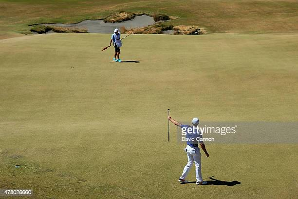 Rory McIlroy of Northern Ireland celebrates after holing a long birdie putt on the 13th green as his caddie JP Fitzgerald looks on during the final...
