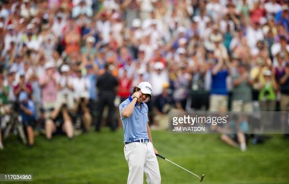 Rory McIlroy of Northern Ireland celebrates after sinking his final putt and winning the 111th US Open by eight strokes over Jason Day with a record...