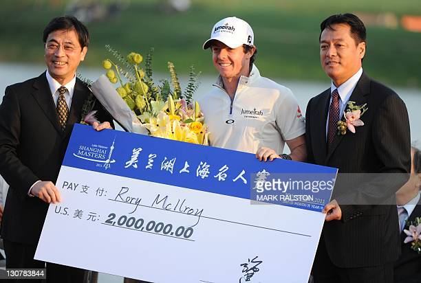 Rory McIlroy of Northern Ireland celebrates his win with his USD$2 million cheque after finishing at 18 under par on the final day of the Lake...