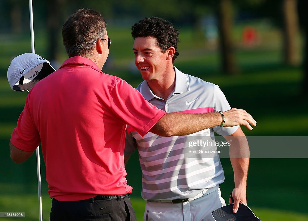 Rory McIlroy of Northern Ireland celebrates with caddie J.P. Fitzgerald after his winning putt on the 18th green during the final round of the World Golf Championships-Bridgestone Invitational at Firestone Country Club South Course on August 3, 2014 in Akron, Ohio.