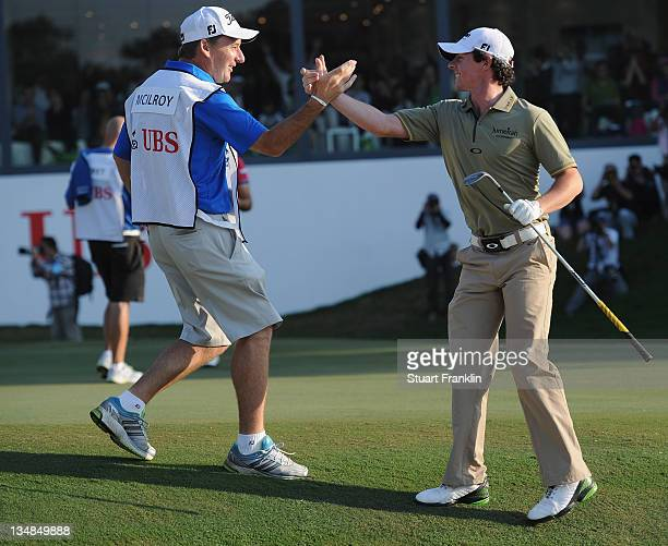 Rory McIlroy of Northern Ireland celebrates with his caddie JP Fitzgerald after holein out his bunker shot on the 18th hole during the final round of...