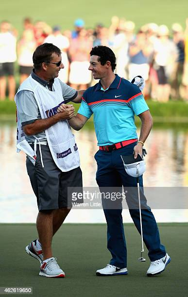 Rory McIlroy of Northern Ireland celebrates with his caddie JP Fitzgerald after winning the Omega Dubai Desert Classic on the Majlis Course at the...