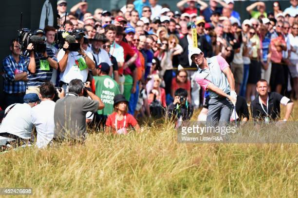 Rory McIlroy of Northern Ireland chips to the fifth green as media and a gallery of patrons look on during the final round of The 143rd Open...