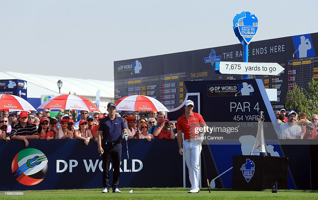 Rory McIlroy of Northern Ireland follows his drive from the first tee watched by Luke Donald of England (l) during the final round of the 2012 DP World Tour Championship on the Earth Course at Jumeirah Golf Estates on November 25, 2012 in Dubai, United Arab Emirates.