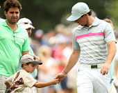 Rory McIlroy of Northern Ireland hands a young fan a ball as he walks from the 10th green to the 11th tee during the final round of The Barclays at...