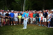 Rory McIlroy of Northern Ireland hits a shot a from the rough on the fourth hole as a gallery of patrons look on during the third round of the 96th...