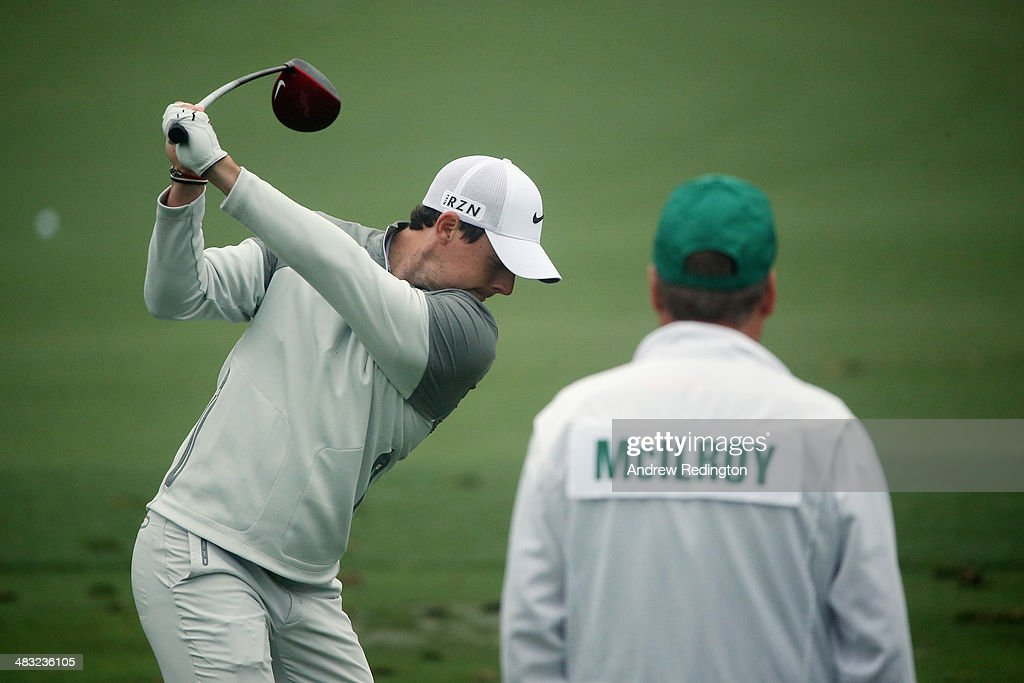 Rory McIlroy of Northern Ireland hits a shot as his caddie, J. P. Fitzgerald, looks on during a practice round prior to the start of the 2014 Masters Tournament at Augusta National Golf Club on April 7, 2014 in Augusta, Georgia.