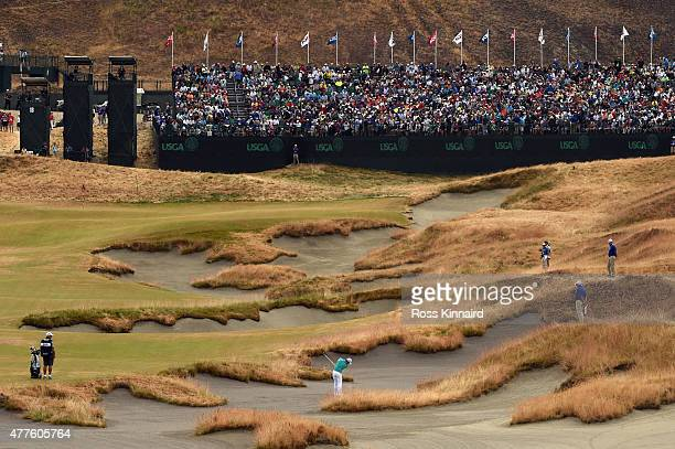 Rory McIlroy of Northern Ireland hits his second shot on the 18th hole during the first round of the 115th US Open Championship at Chambers Bay on...