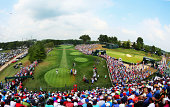 Rory McIlroy of Northern Ireland hits his tee shot on the first hole as a gallery of fans look on during the final round of the 96th PGA Championship...