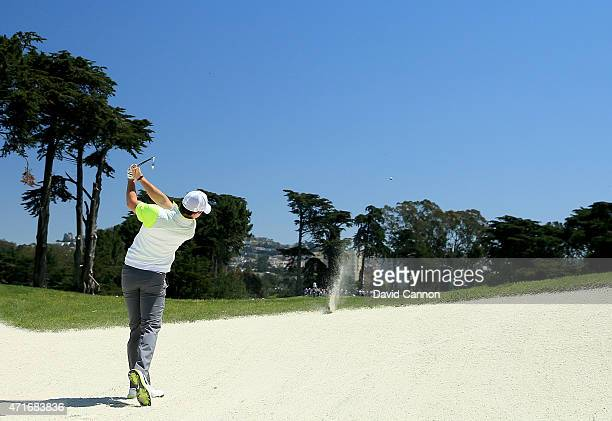 Rory McIlroy of Northern Ireland hits the lip of the bunker with his second shot on the par 5 first hole during round two of the World Golf...