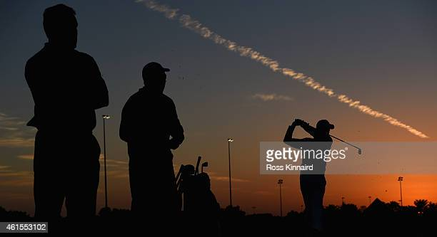Rory McIlroy of Northern Ireland is watched by his coach Michael Bannon and caddie JP Fitzgerald on the practice range during the first round of the...