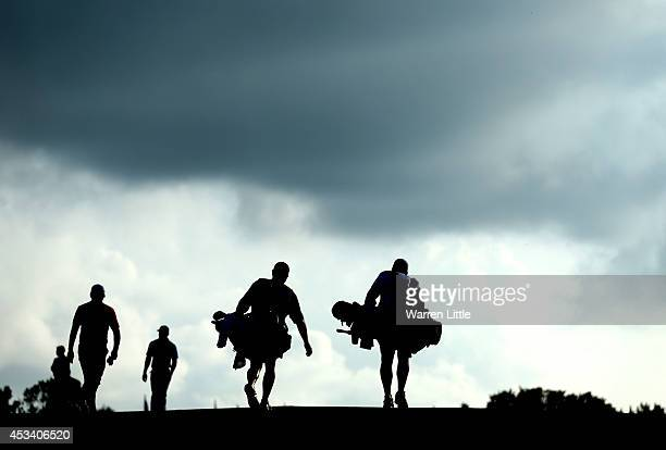 Rory McIlroy of Northern Ireland Jason Day of Australia caddie JP Fitzgerald and caddie Colin Swatton walk up the 17th hole during the third round of...