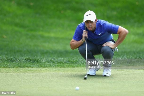 Rory McIlroy of Northern Ireland lines up a putt on the 18th green during the final round of the Travelers Championship at TPC River Highlands on...