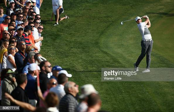 Rory McIlroy of Northern Ireland plays his second shot into the 14th green during the first round of the Omega Dubai Desert Classic on the Majlis...