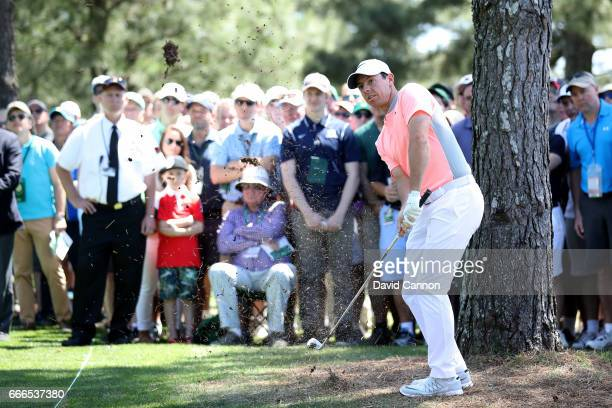 Rory McIlroy of Northern Ireland plays his second shot on the first hole as patrons look on during the final round of the 2017 Masters Tournament at...