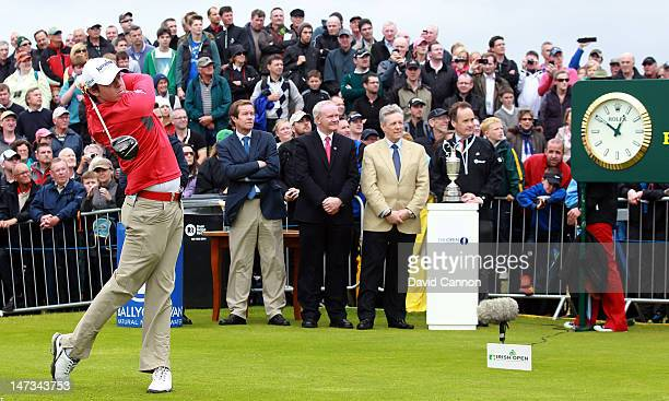 Rory McIlroy of Northern Ireland plays his tee shot at the par 4 1st hole watched by George O'Grady the Chief Executive of The European Tour Martin...