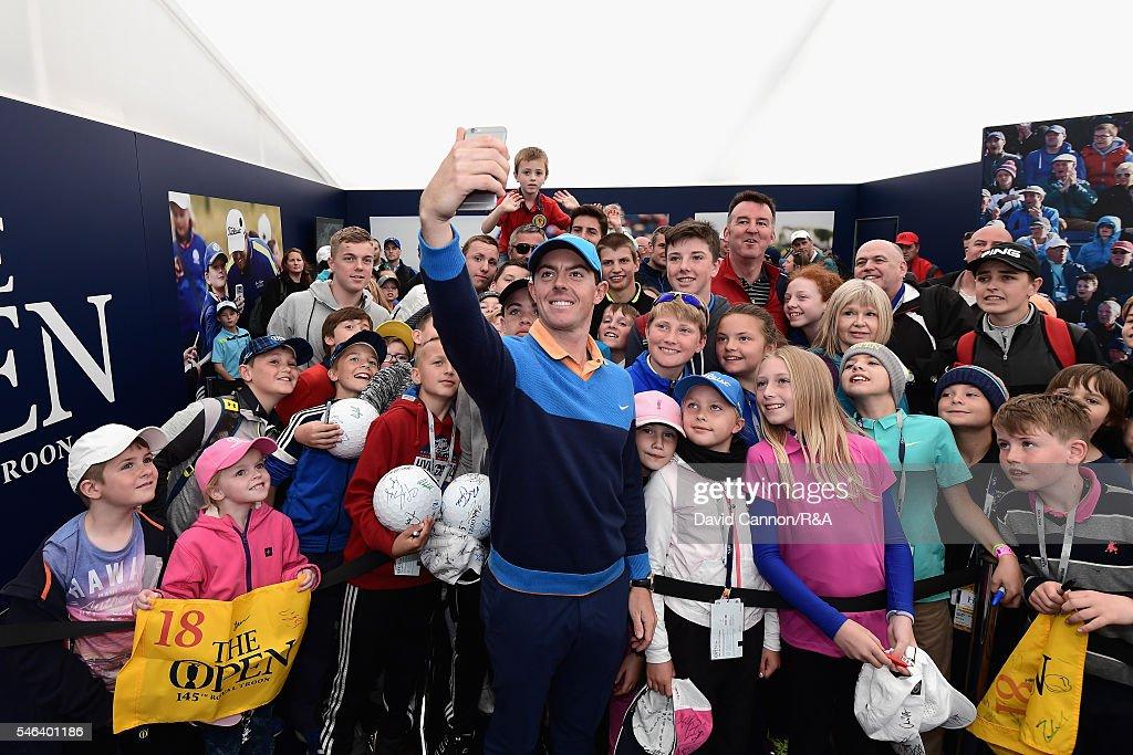 Rory McIlroy of Northern Ireland poses for a selfie with children during previews ahead of the 145th Open Championship at Royal Troon on July 12, 2016 in Troon, Scotland.