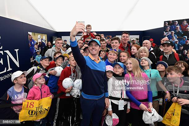 Rory McIlroy of Northern Ireland poses for a selfie with children during previews ahead of the 145th Open Championship at Royal Troon on July 12 2016...