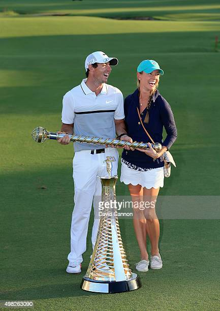 Rory McIlroy of Northern Ireland poses with his girlfriend Erica Stoll and the DP World Tour Championship and Race to Dubai trophy after his one shot...