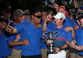 Rory McIlroy of Northern Ireland poses with the Australian Open trophy and greenkeeping staff after victory during day four of the 2013 Australian...