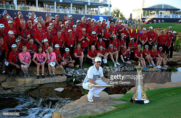 Rory McIlroy of Northern Ireland poses with the DP World Tour Championship trophy and a group of course marshals after his one shot win in the final...