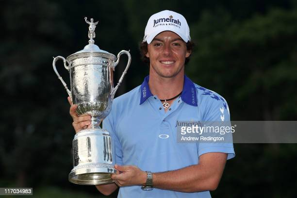 Rory McIlroy of Northern Ireland poses with the trophy after his eightstroke victory on the 18th green during the 111th US Open at Congressional...