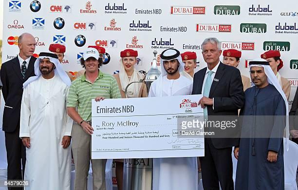 Rory McIlroy of Northern Ireland poses with the trophy alongside Sheikh Majid bin Mohammed bin Rashid Al Maktoum Chairman of Dubai Culture and Arts...