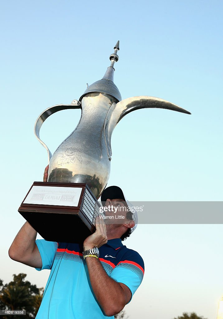 Rory McIlroy of Northern Ireland raises the trophy after winning the Omega Dubai Desert Classic on the Majlis Course at the Emirates Golf Club on...