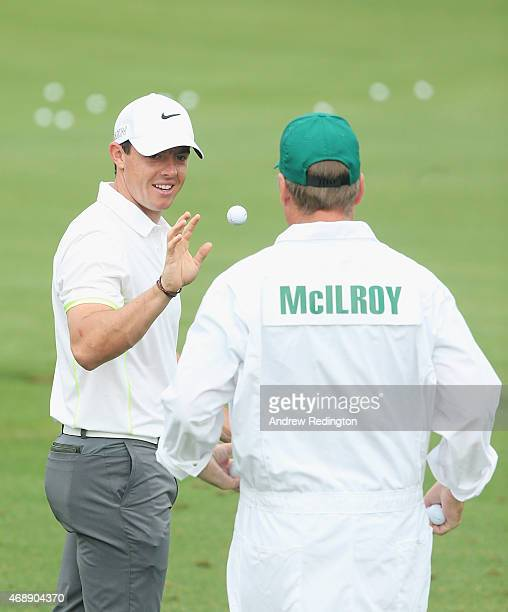 Rory McIlroy of Northern Ireland reaches for a golf ball alongside his caddie JP Fitzgerald on the practice ground during a practice round prior to...