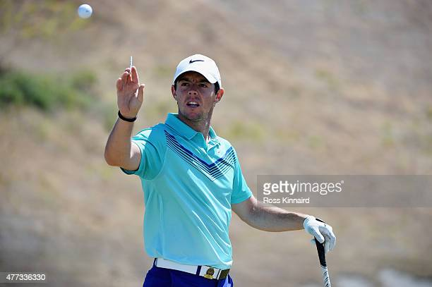 Rory McIlroy of Northern Ireland reaches for a golf ball on the practice ground during a practice round prior to the start of the 115th US Open...