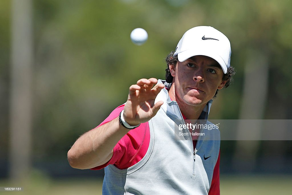 Rory McIlroy of Northern Ireland reaches for a golf ball on the practice ground during the first round of the WGC-Cadillac Championship at the Trump Doral Golf Resort & Spa in Miami, Florida.