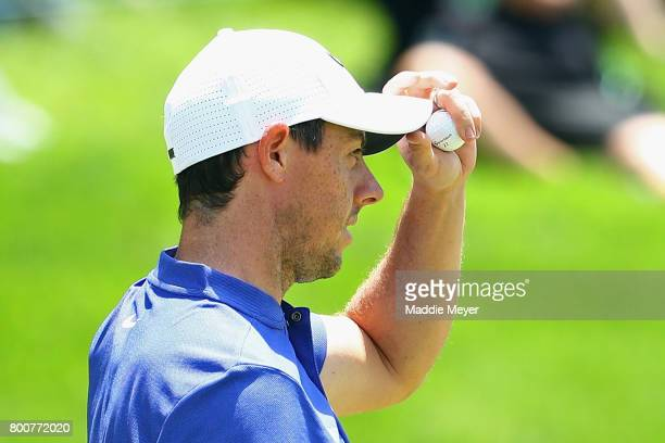Rory McIlroy of Northern Ireland reacts after putting on the 18th green during the final round of the Travelers Championship at TPC River Highlands...