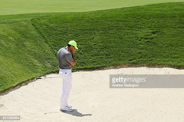 Rory McIlroy of Northern Ireland reacts to a bunker shot on the ninth hole during the continuation of the second round of the US Open at Oakmont...
