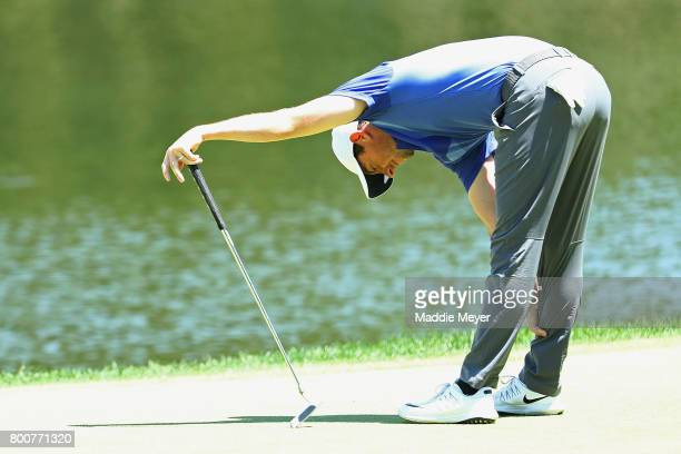 Rory McIlroy of Northern Ireland reacts to a putt on the 16th green during the final round of the Travelers Championship at TPC River Highlands on...