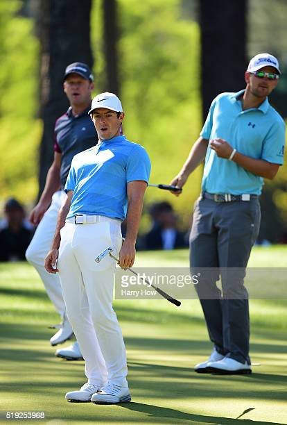 Rory McIlroy of Northern Ireland reacts to a putt on the sixth green as Jamie Donaldson of Wales and Bernd Wiesberger of Austria look on during a...