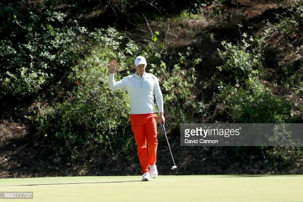 Rory McIlroy of Northern Ireland reacts to making a putt for birdie on the 12th green during the third round of the 2017 Masters Tournament at...