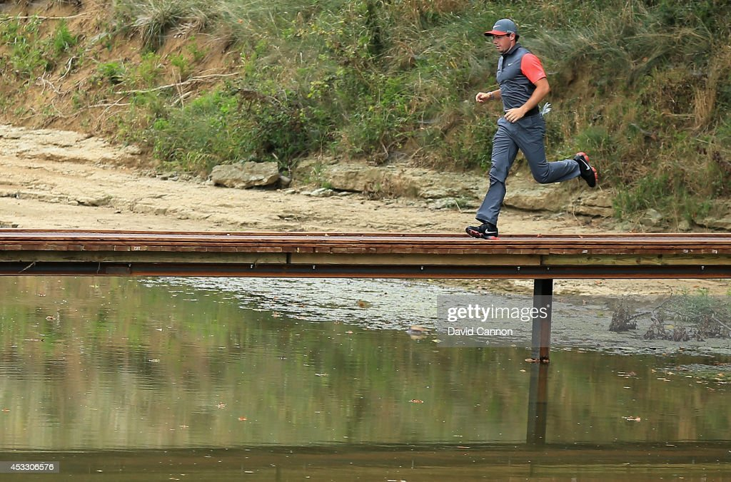 Rory McIlroy of Northern Ireland runs over the bridge from the ninth tee to the ninth fairway after a bathroom break during the first round of the 96th PGA Championship at Valhalla Golf Club on August 7, 2014 in Louisville, Kentucky.