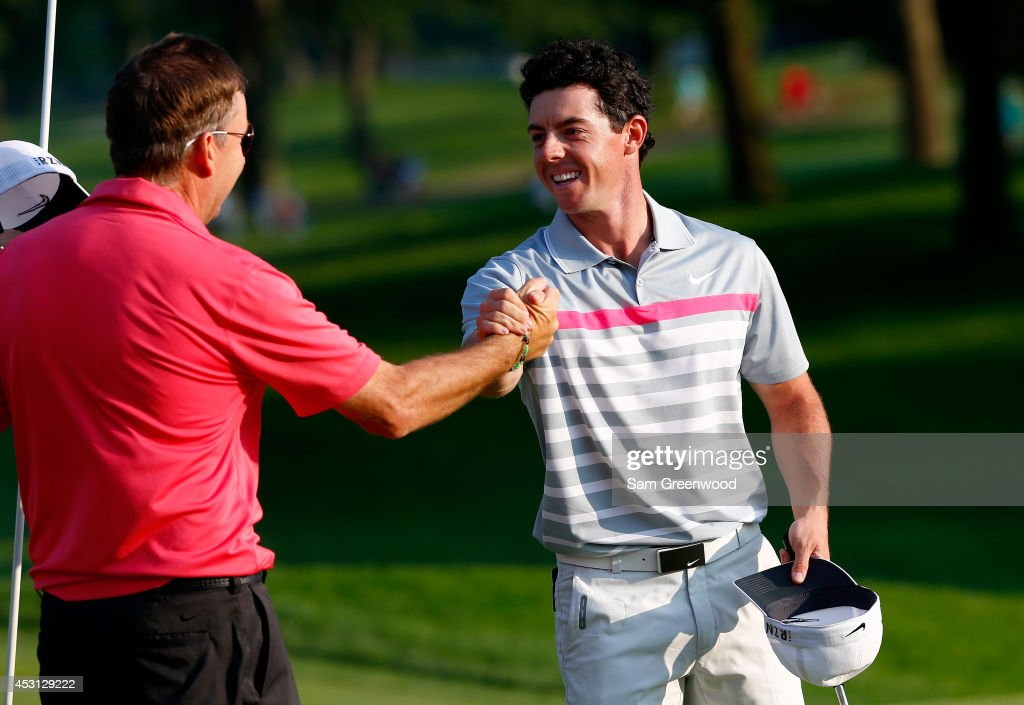 Rory McIlroy of Northern Ireland shakes hands with caddie J.P. Fitzgerald after his winning putt on the 18th green during the final round of the World Golf Championships-Bridgestone Invitational at Firestone Country Club South Course on August 3, 2014 in Akron, Ohio.