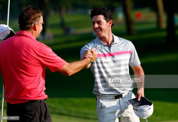 Rory McIlroy of Northern Ireland shakes hands with caddie JP Fitzgerald after his winning putt on the 18th green during the final round of the World...