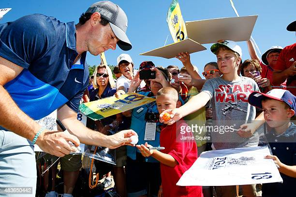 Rory McIlroy of Northern Ireland signs autographs for fans during a practice round prior to the 2015 PGA Championship at Whistling Straits on August...