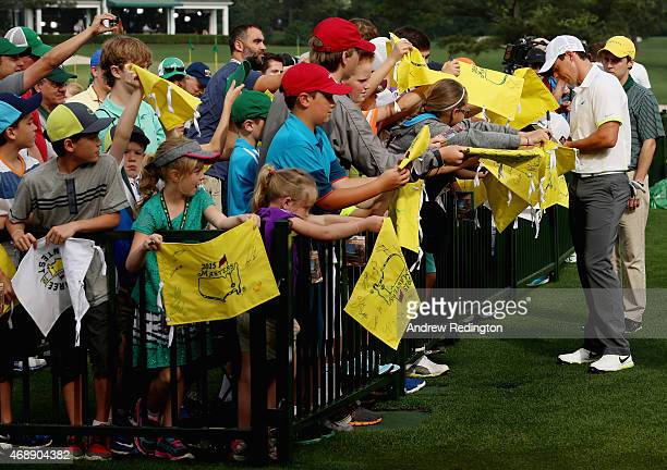 Rory McIlroy of Northern Ireland signs autographs for fans near the practice ground during a practice round prior to the start of the 2015 Masters...