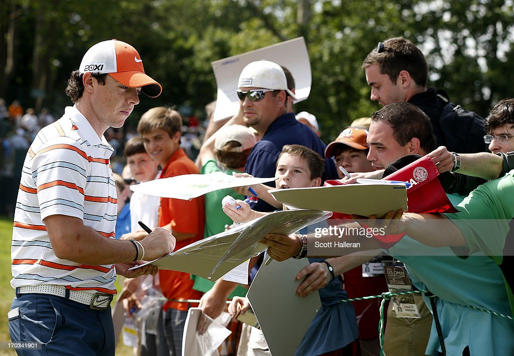 Rory McIlroy of Northern Ireland signs his autograph for fans during a practice round prior to the start of the 113th U.S. Open at Merion Golf Club on June 11, 2013 in Ardmore, Pennsylvania.