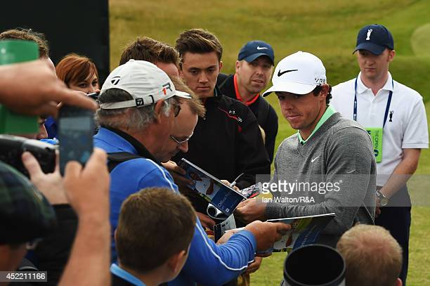 Rory McIlroy of Northern Ireland signs his autograph for fans during a practice round prior to the start of the 143rd Open Championship at Royal...